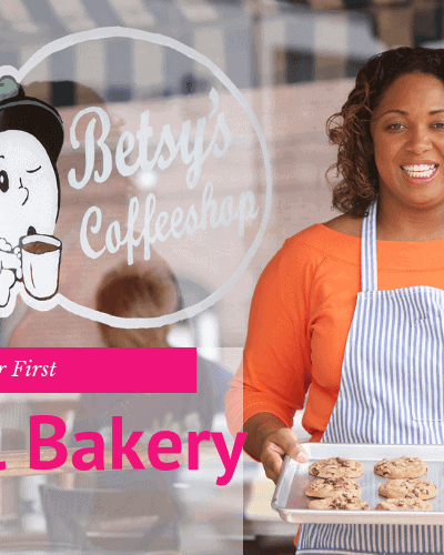 Black woman holding a tray of chocolate chip cookies in front of her bakery and coffee shop
