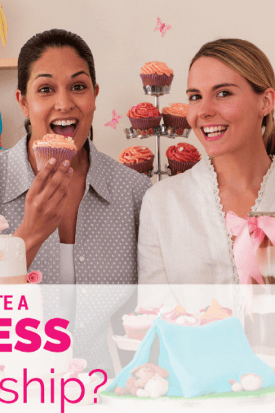 two young women business partners holding cupcakes in their custom cake shop