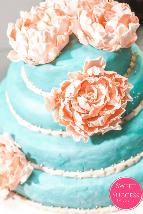 turquoise blue tiered cake with pink sugar handmade flowers