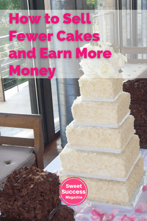 A tall cake five tier cake with white chocolate shavings and two smaller chocolate cakes on each side
